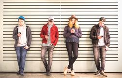 Friends group using smartphone against wall at university college backyard break - Young people addicted by mobile smart phone stock image