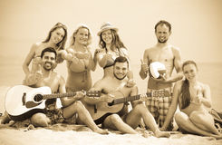 Friends with guitar at beach. Group of cheerful smiling young adults relaxing on sand at beach with guitar. Selective focus stock photography