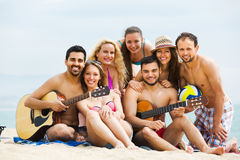 Friends with guitar at beach Stock Images