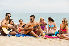 Friends with guitar at beach Stock Photos