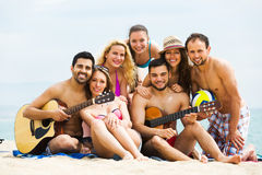 Friends with guitar at beach Stock Photography