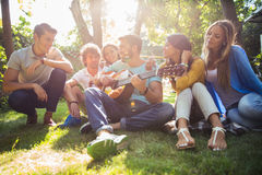 Friends with guitar having fun outdoor. Group of happy friends with guitar having fun outdoor Royalty Free Stock Photography