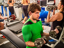 Friends in gym fitness workout equipment. Man do dumbbell exercise. Stock Image
