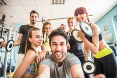 Friends in a gym. Group of sportive people in a gym taking selfie - Happy sporty friends in a weight room while training - Concepts about lifestyle and sport in Stock Images