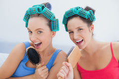 Friends in hair rollers singing into their hairbrushes Royalty Free Stock Photography