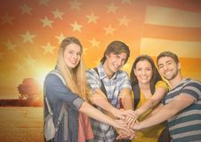 Friends with hands together agaisnt american flag and beautiful landscape Royalty Free Stock Photos