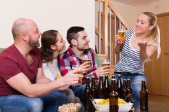 Friends hanging out with beer. Positive happy friends hanging out with beer and snacks at home Royalty Free Stock Image
