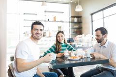Friends Hanging Out In Cafe. Portrait of confident young men drinking coffee with friends in coffee shop stock photography