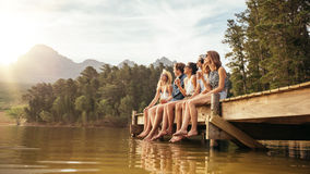 Friends hanging out at the lake. Portrait of relaxed young people sitting on the jetty with beers. Friends hanging out at the lake on a summer day Royalty Free Stock Image