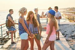 Friends hanging out at the sunny summer seaside. Friends having a pleasant conversation while hanging out at the seaside royalty free stock image
