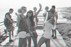 Friends hanging out at the sunny summer seaside. Friends gesturing hi five while hanging out at the seaside with glitch effect royalty free stock photos