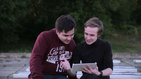 Friends hanging out using digital tablet touchscreen outdoor. stock video