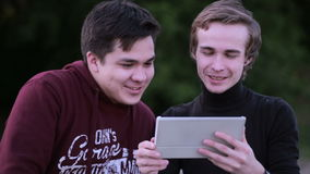 Friends hanging out using digital tablet touchscreen outdoor. stock video footage
