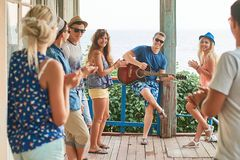 Friends hanging out on vacation at an old wooden cabin porch by the sea while one of them is playing guitar and others royalty free stock image