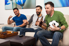 Friends hanging out and watching a game Royalty Free Stock Images