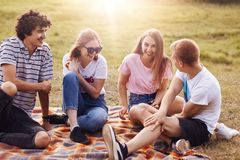 Friends, happiness and leisure concept. Photo of friendly teenagers meet together on nature, have picnic, tell each other funny st. Ories, enjoy summer weather Royalty Free Stock Image