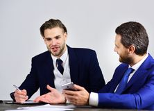 Friends with happy faces discuss startup and surf internet. Business people hold smartphone, pen and notebook. Businessman consults with financial analyst Royalty Free Stock Image
