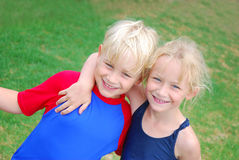 Friends and happy kids. Outdoor portrait of a Caucasian blond boy with a white girl child embracing him with happy smiling facial expression royalty free stock images