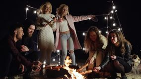 Friends have fun in evening in open air near fire roast the sausages and drink alcoholic beverages