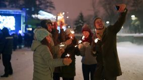 Friends have fun partying with sparklers and doing selfie photo on smartphone at Christmas market. People jump and dance