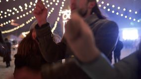 Friends have fun partying with sparklers and explode confetti cannon at Christmas market. Cheerful people jump and dance