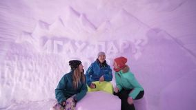Friends have fun on the ski resort. Ice hotel: stunning interior in icy room at ice hotel. Frozen room made of ice and