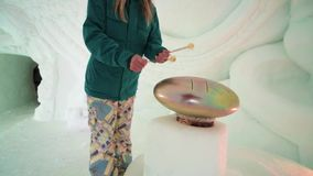 Friends have fun on the ski resort. Tourist play with Hang drum music instrument. Stunning interior in icy room at Ice