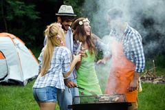 Friends having a barbecue party in nature. While having fun royalty free stock photo