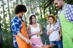 Friends having a barbecue party in nature while having fun royalty free stock images