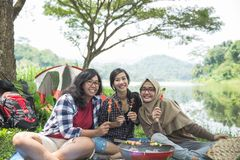 Friends having barbecue together. Happy asian friends having barbecue together while camping out in the wood Royalty Free Stock Images