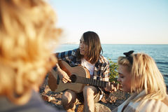 Friends Having Bonfire Party. Group of young friends relaxing around campfire and listening to music, handsome Asian men playing guitar, picturesque seascape on Royalty Free Stock Images