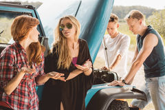 Friends having car problem. Young friends having car problem during trip Royalty Free Stock Photography