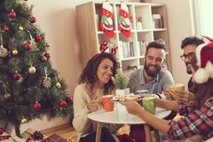 Friends having Christmas morning coffee. Group of friends sitting next to a Christmas tree, eating Christmas cookies drinking coffee and having fun. Focus on the Stock Photography