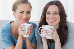 Friends having coffee and looking at camera Stock Images