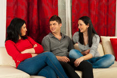 Friends having conversation on sofa. Three happy friends having conversation home and sitting together on sofa Stock Image