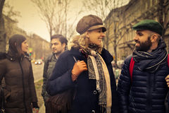 Friends having a conversation in the street. Group of friends talking in the street while they visit a city Royalty Free Stock Photography