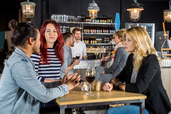 Friends Having Conversation At Table In Bar. Young friends having conversation at table in bar Royalty Free Stock Photo