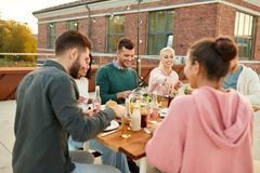 Friends having dinner or rooftop party in summer stock image