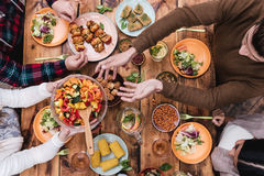 Friends having dinner. Top view of four people having dinner together while sitting at the rustic wooden table Stock Image