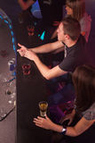 Friends having a drink. In a disco Royalty Free Stock Photos