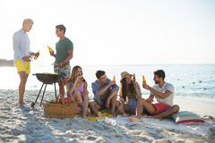 Friends having drinks by barbecue at beach against sky Stock Images