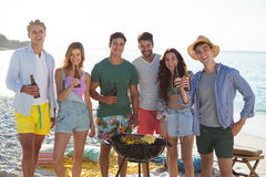 Friends having drinks by barbecue at beach Royalty Free Stock Image