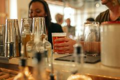 Friends having drinks together at the counter of a bar stock photography