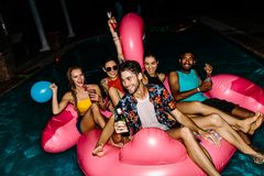 Friends having evening pool party. Group of men and women having beers on an inflatable pool float mattress in evening. Friends hanging out together in a pool Stock Photos