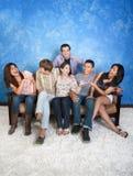 Friends Having Fun. Group of six happy friends on sofa having fun Stock Image