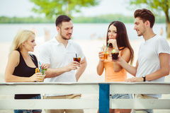 Friends having fun at the bar outdoors, drinking cocktails. Royalty Free Stock Image