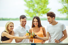 Friends having fun at the bar outdoors, drinking cocktails. Royalty Free Stock Photos