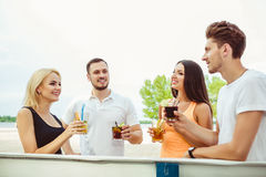 Friends having fun at the bar outdoors, drinking cocktails. Stock Image
