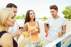 Friends having fun at the bar outdoors, drinking cocktails. Royalty Free Stock Images