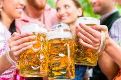 Friends having fun in beer garden while clinking glasses. Five friends, men and women, having fun in beer garden clinking glasses with beer stock photos